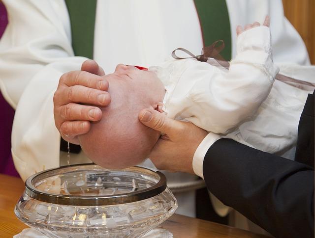 """""""Pappi sivelee vettä vauvan otsalle kastemaljan päällä."""""""